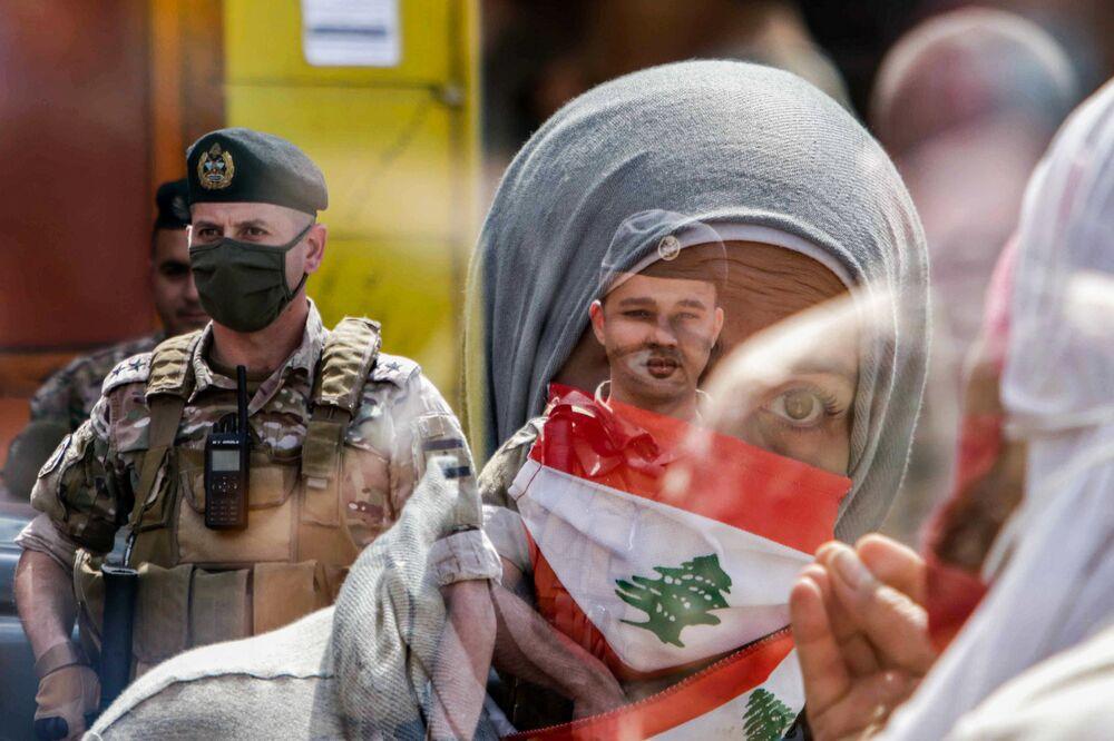 Participante de manifestação no Líbano com máscara com o desenho da bandeira do seu país em frente a soldado na cidade libanesa de Trípoli