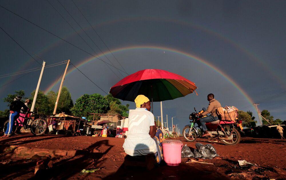 Arco-íris duplo por cima de mulher carregando guarda-chuva e vendendo comida em via do condado de Siaya, no Quênia