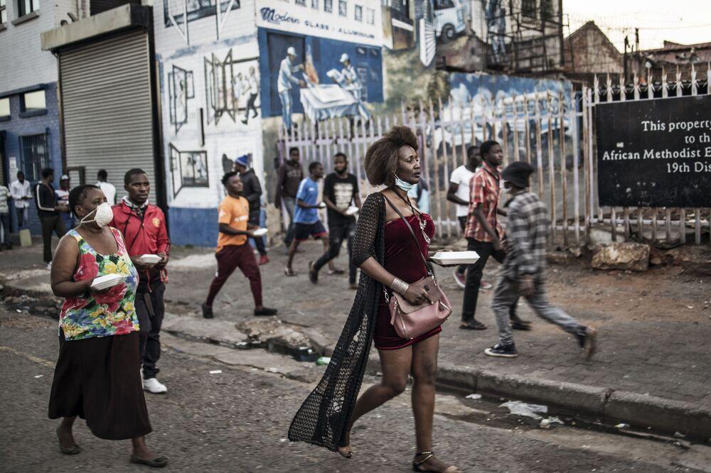 Moradores de Joanesburgo, África do Sul, recebem comida grátis destinada aos cidadãos de baixa renda