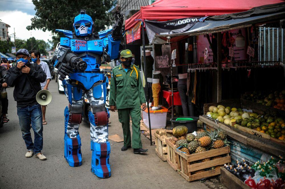 Homem vestido de transformer conclama moradores de Bandung, na Indonésia, a permanecerem em casa durante a pandemia