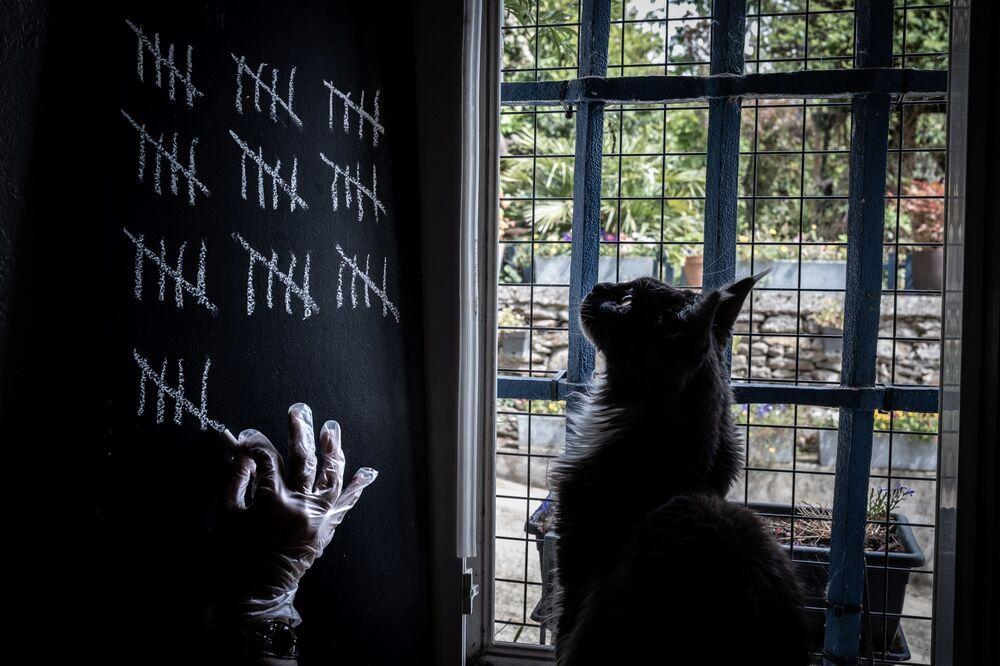 Pessoa marca com giz os dias de confinamento devido à pandemia de COVID-19 em Givors, na França