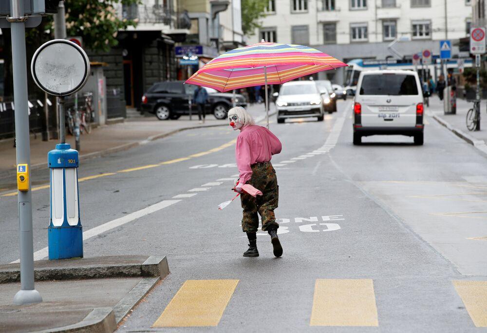 Homem vestido de palhaço atravessa rua de Zurique, na Suíça, durante a propagação da COVID-19