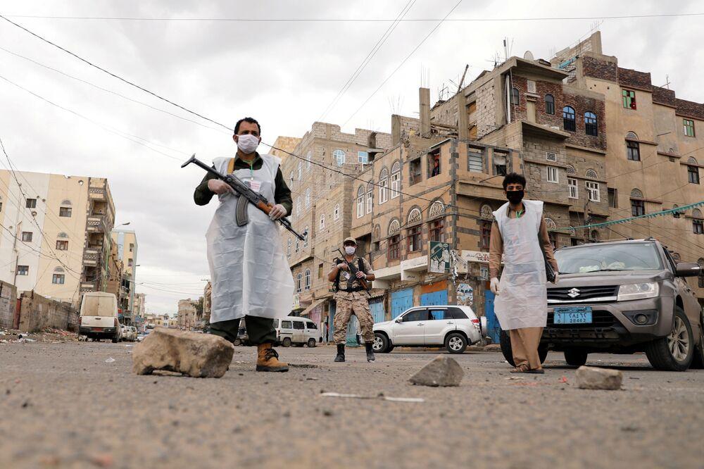 Agentes de segurança iemenitas usam máscaras durante toque de recolher devido à pandemia na capital do Iêmen, Sanaa