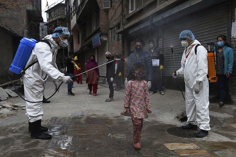 Agentes de saúde borrifam desinfetante em criança durante isolamento total imposto pelo governo em Catmandu, Nepal