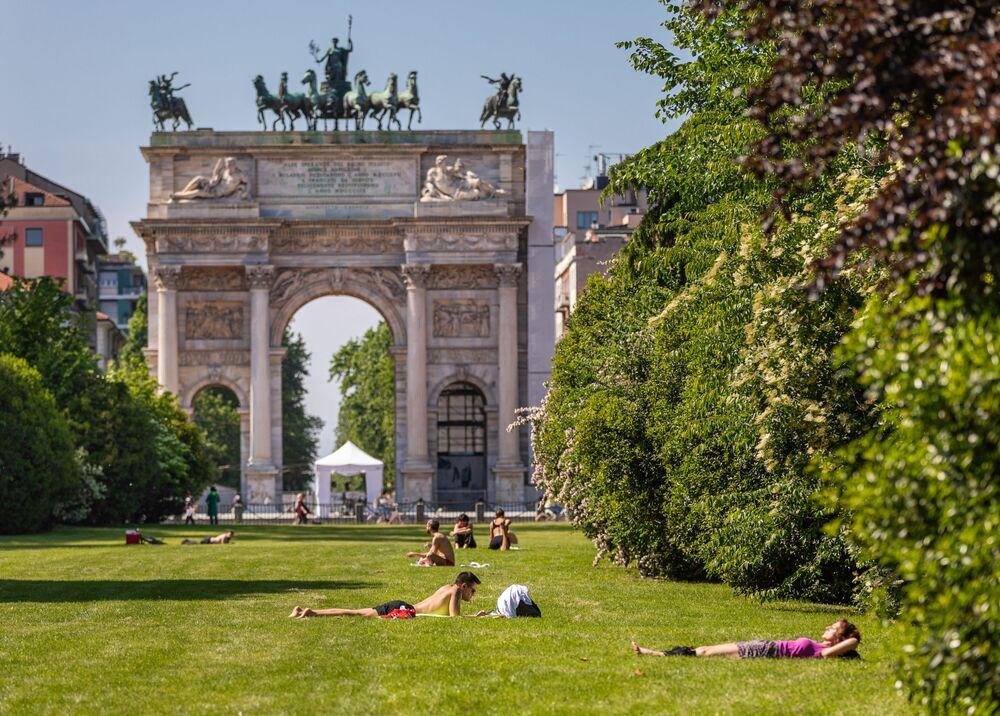 Pessoas descansando em um dos parques de Milão, Itália