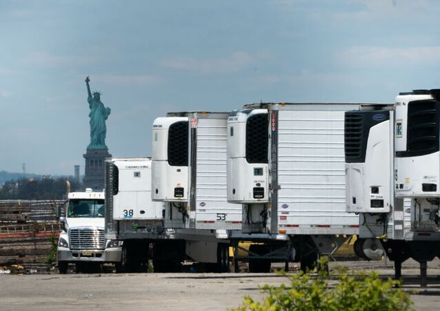 Refrigeradores móveis com corpos de falecidos durante a pandemia, no bairro de Brooklyn, em Nova York, tendo como fundo a estátua da Liberdade