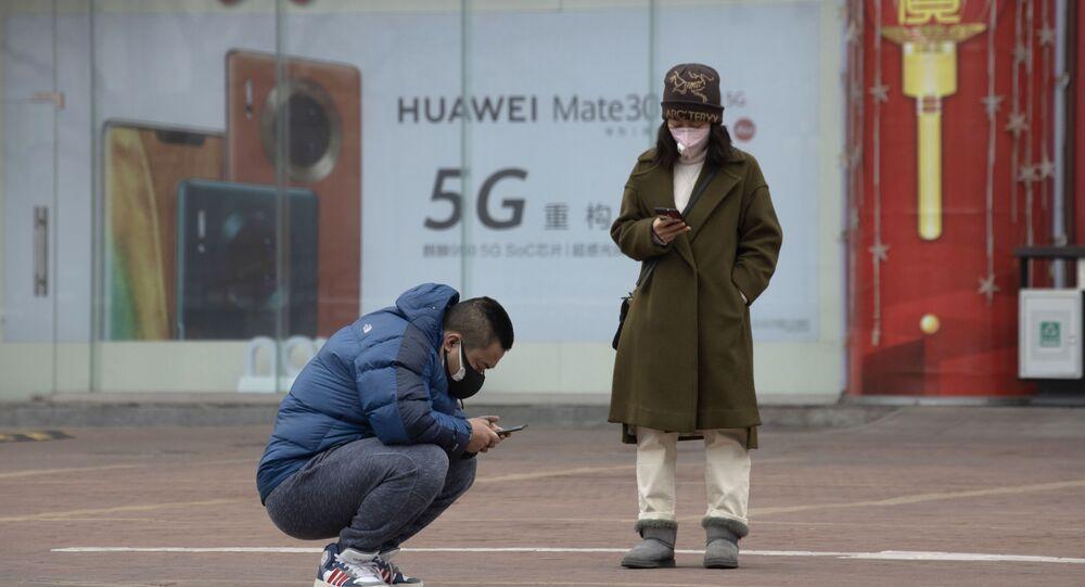 Moradores usando máscaras verificam seus celulares perto de um anúncio para smartphones 5G do gigante tecnológico chinês Huawei em Pequim, 8 de março de 2020