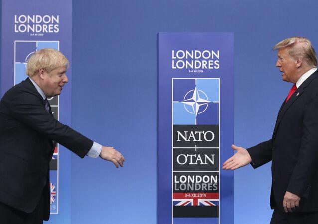 O primeiro-ministro britânico Boris Johnson, à esquerda, estende a mão para cumprimentar o presidente norte-americano Donald Trump durante as chegadas oficiais para uma reunião de líderes da OTAN, no hotel e resort The Grove em Watford, Hertfordshire, Reino Unido, 4 de dezembro de 2019