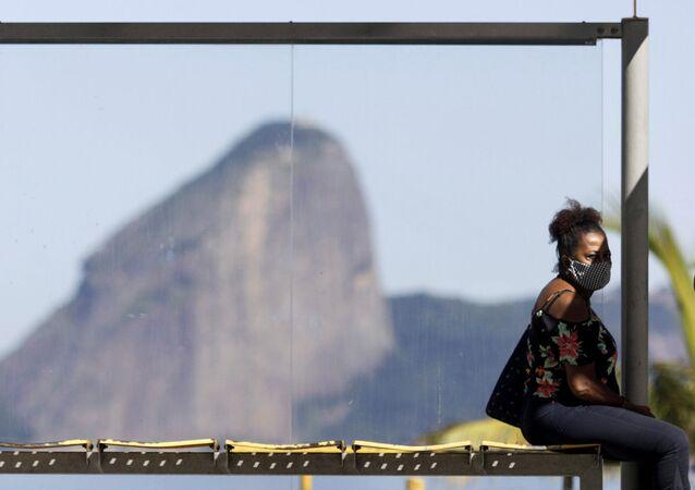 Mulher usando máscara protetora em ponto de ônibus, no Rio de Janeiro, 11 de maio de 2020