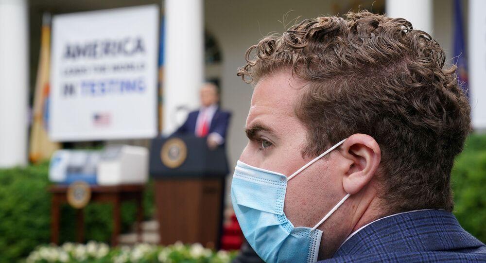 Repórter com máscara protetora durante conferência de imprensa do presidente dos EUA, Donald Trump, na Casa Branca, em Washington, 11 de maio de 2020