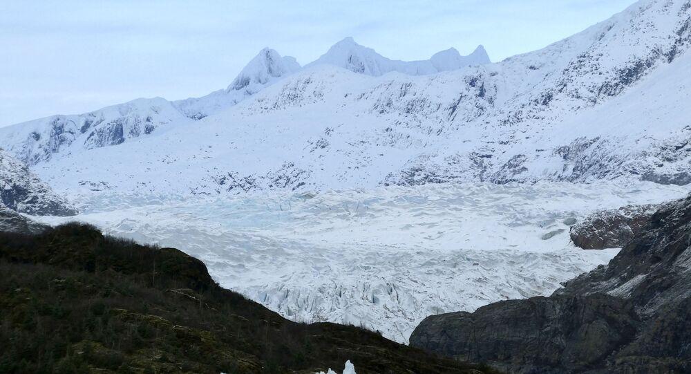 Um iceberg no lago Mendenhall, com a geleira Mendenhall e as montanhas mostradas ao fundo em Juneau, Alasca, EUA, 29 de novembro de 2019