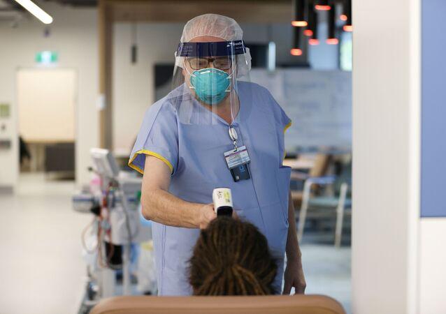 Enfermeiro verifica temperatura de paciente em clínica de testes para coronavírus, Sydney, Austrália, 12 de maio de 2020