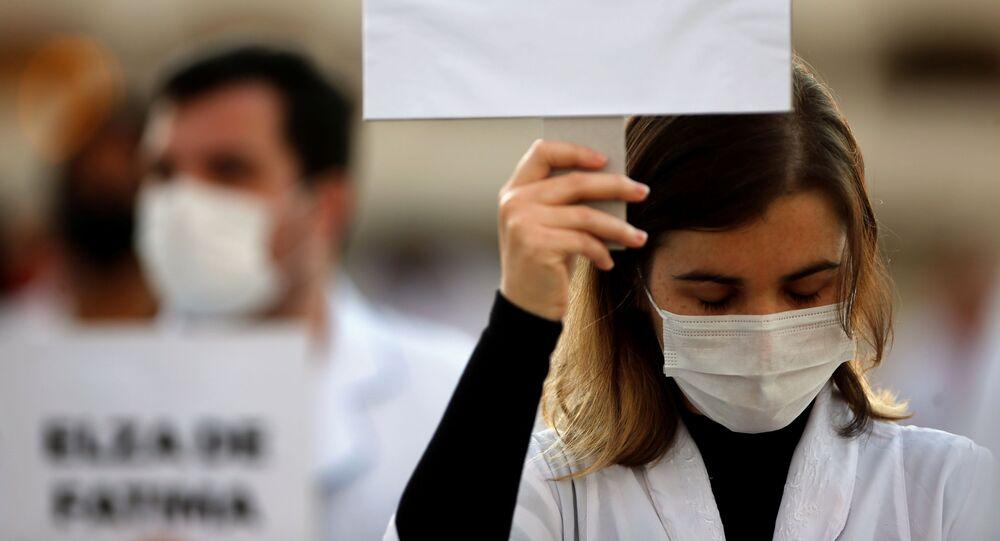 Enfermeira empunha cartaz com nome de colega vítima da COVID-19, durante protesto em Brasília, 12 de maio de 2020