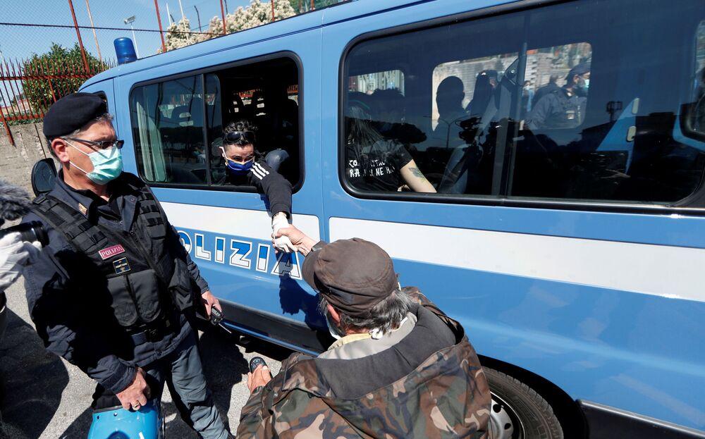 Manifestante com cadeira de rodas diante de ônibus com presidiárias na capital italiana