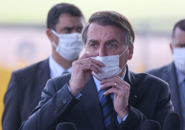 O presidente Jair Bolsonaro fala com apoiadores e com a imprensa ao sair do Palácio da Alvorada, em Brasília.