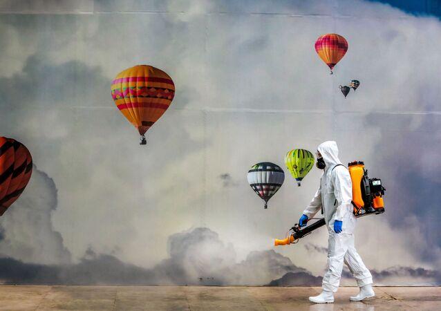 Funcionário da prefeitura usa roupa protetora em desinfecção de centro comercial em Caxias do Sul, 13 de maio de 2020
