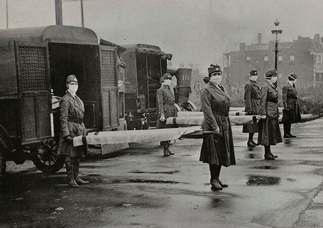 Mulheres mascaradas seguram macas perto de ambulâncias durante a pandemia da gripe espanhola em St. Louis, Missouri, Estados Unidos, outubro de 1918