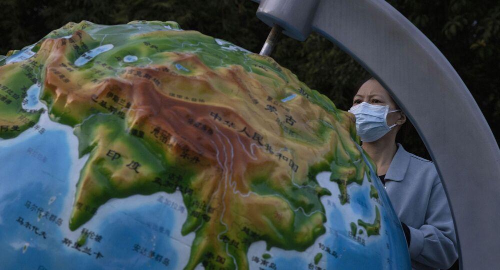 Mulher usando máscara contra coronavírus olha para globo mostrando a China, em Wuhan, na província de Hubei, 15 de abril de 2020
