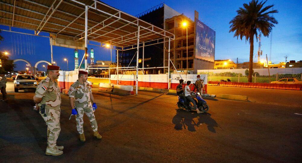 Soldados iraquianos ficam de guarda em uma rua, impondo o toque de recolher para evitar a propagação da doença do coronavírus (COVID-19) durante o mês sagrado de jejum do Ramadã, em Bagdá, Iraque, 3 de maio de 2020