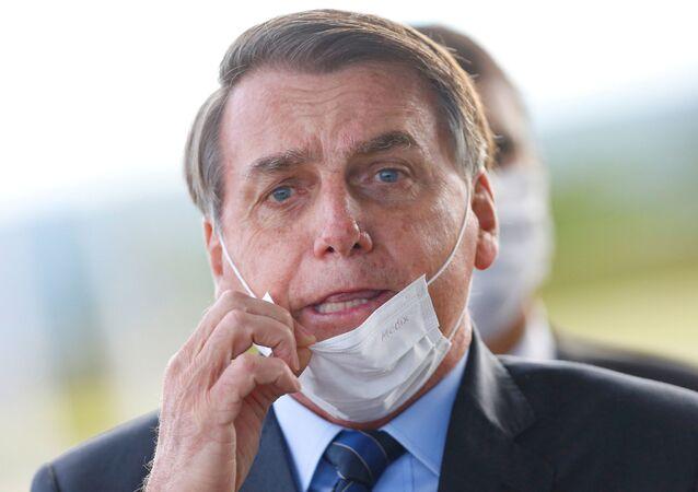 Presidente Jair Bolsonaro ajusta a sua máscara em frente ao Palácio da Alvorada, em Brasília (DF)