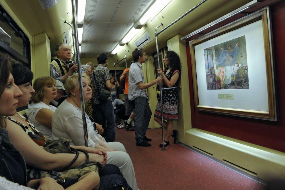 Passageiros viajam em vagão do trem Aquarela do metrô de Moscou