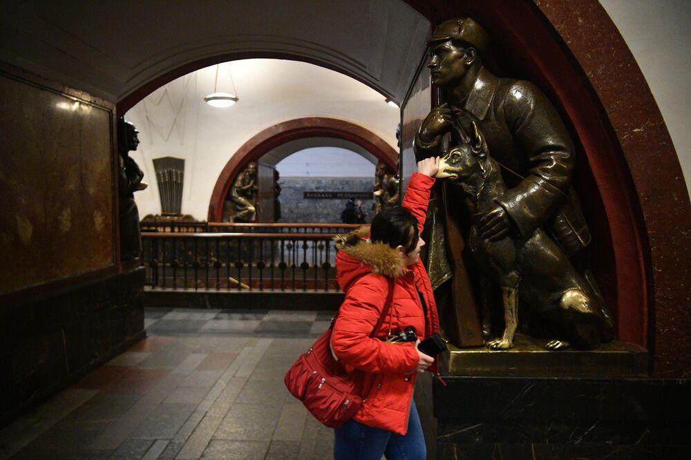 Moça faz tradicional toque em focinho de cachorro, uma estátua na estação Ploschad Revolyutsy do metrô de Moscou