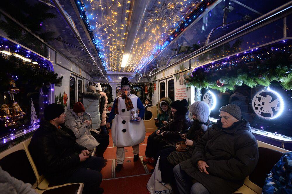 Passageiros em vagão com tema natalino de um trem enfeitado para o Ano Novo no metrô de Moscou