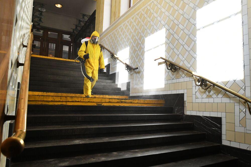 Funcionário do Ministério para Situações de Emergência da Rússia desinfecta uma das passagens da estação de metrô Kievskaya