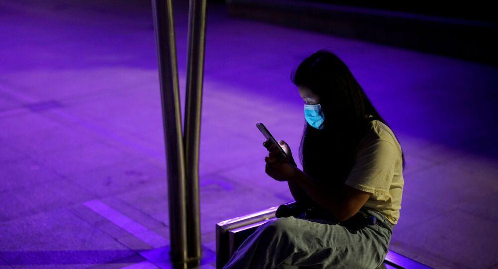 Mulher com máscara facial protetora usa telefone em um parque de Wuhan, a cidade chinesa mais atingida pela doença COVID-19, província de Hubei, China, 15 de maio de 2020