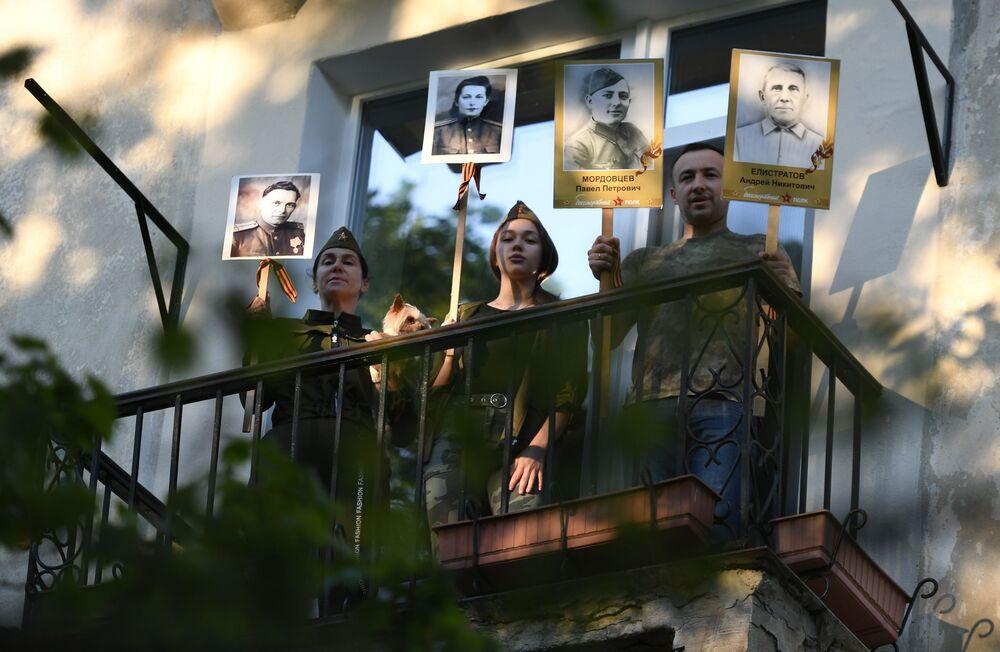 Pessoas em casa cantando canções na varanda com retratos de seus parentes que participaram na Grande Guerra pela Pátria, em Sevastopol, Crimeia, Rússia