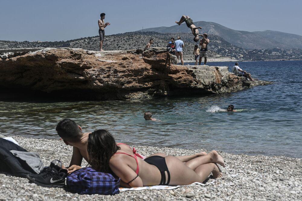 Pessoas tomando banhos de sol nos subúrbios de Atenas, Grécia.