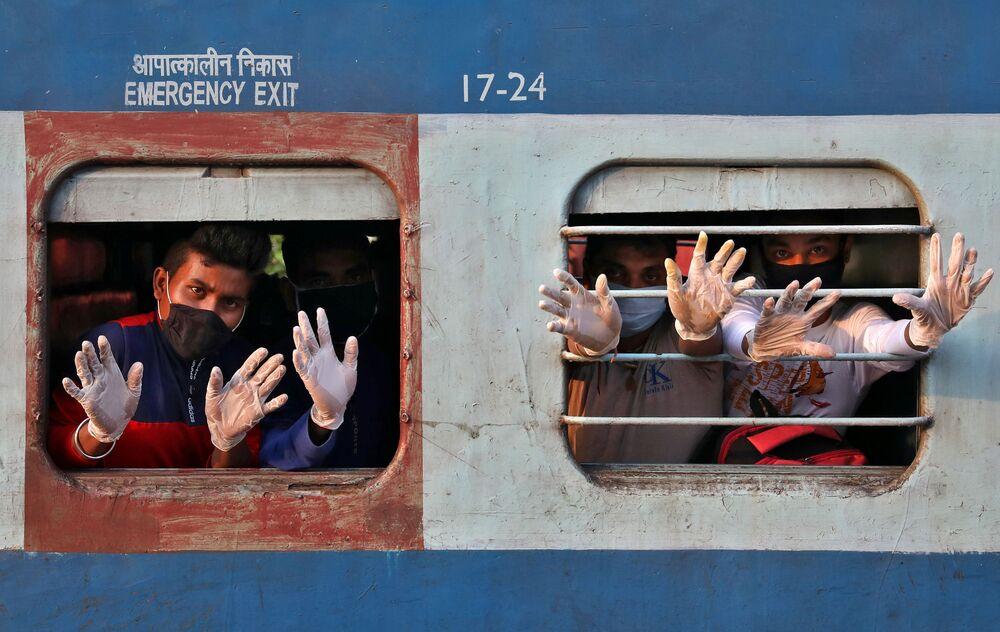Passageiros acenando com as mãos de uma janela de trem na Índia