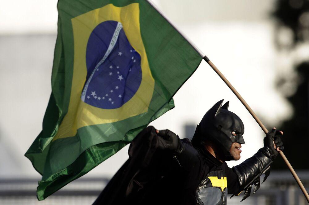 Homem vestido com traje de Batman e segurando bandeira nacional junta-se a multidão em frente ao Palácio do Planalto, demonstrando seu apoio ao presidente Jair Bolsonaro.