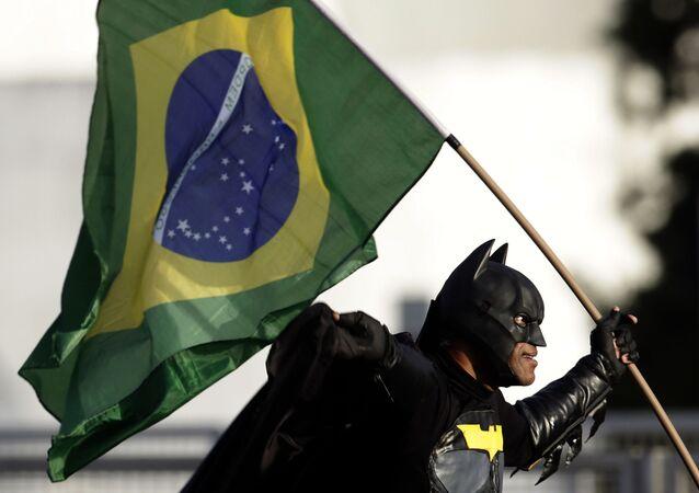 Homem vestido com traje de Batman e segurando bandeira nacional junta-se a multidão em frente ao Palácio do Planalto, demonstrando seu apoio ao presidente Jair Bolsonaro