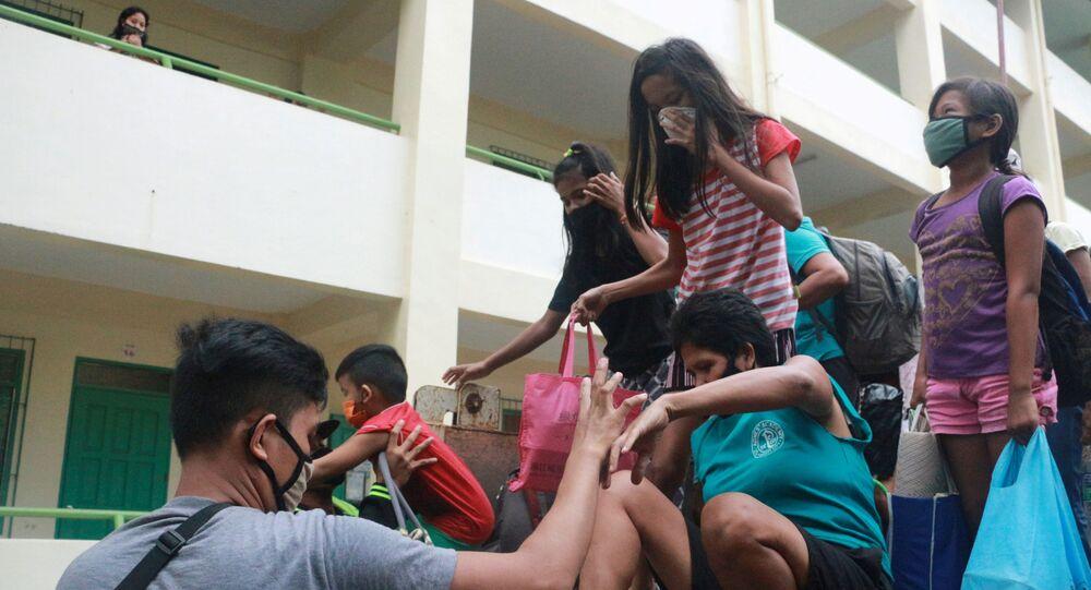 Moradores usando máscaras de proteção contra a COVID-19 chegam a uma escola transformada em abri contra o tufão Vongfong, na cidade de Legazpi, nas Filipinas, em 14 de maio de 2020.
