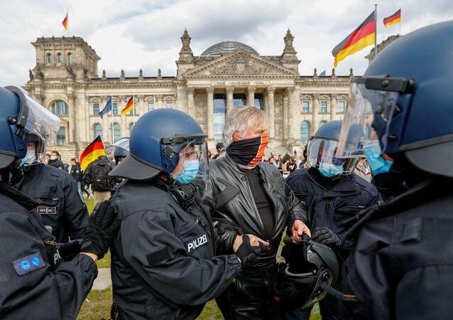 Em frente ao Reichstag, em Berlim, policiais com máscaras detém um manifestante que protestava contra as medidas de isolamento social na Alemanha durante a pandemia da COVID-19.