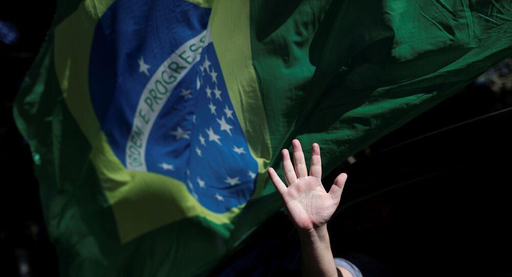 Pessoa acena da janela do carro durante manifestação em apoio ao presidente Jair Bolsonaro, em São Paulo, 17 de maio de 2020