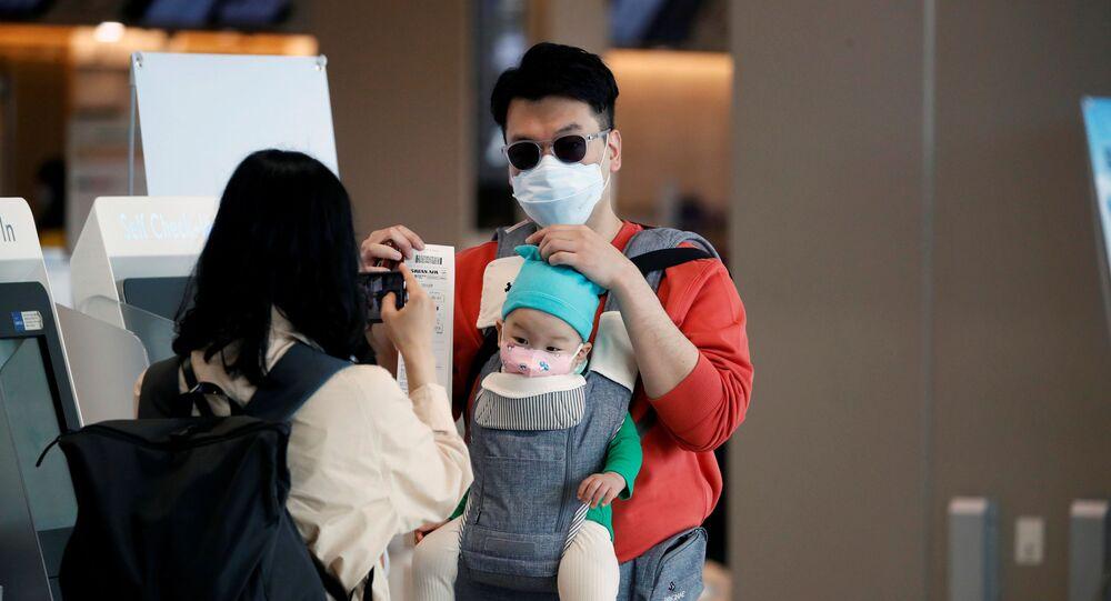 Mulher usando uma máscara para evitar a propagação do coronavírus (COVID-19) tira uma fotografia de seu marido e filho após o check-in no aeroporto internacional de Gimpo em Seul, Coreia do Sul, 1º de maio de 2020