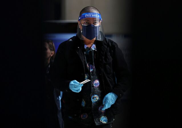 Homem com máscara facial, viseira e luvas é visto na Estação Waterloo, em Londres, Reino Unido