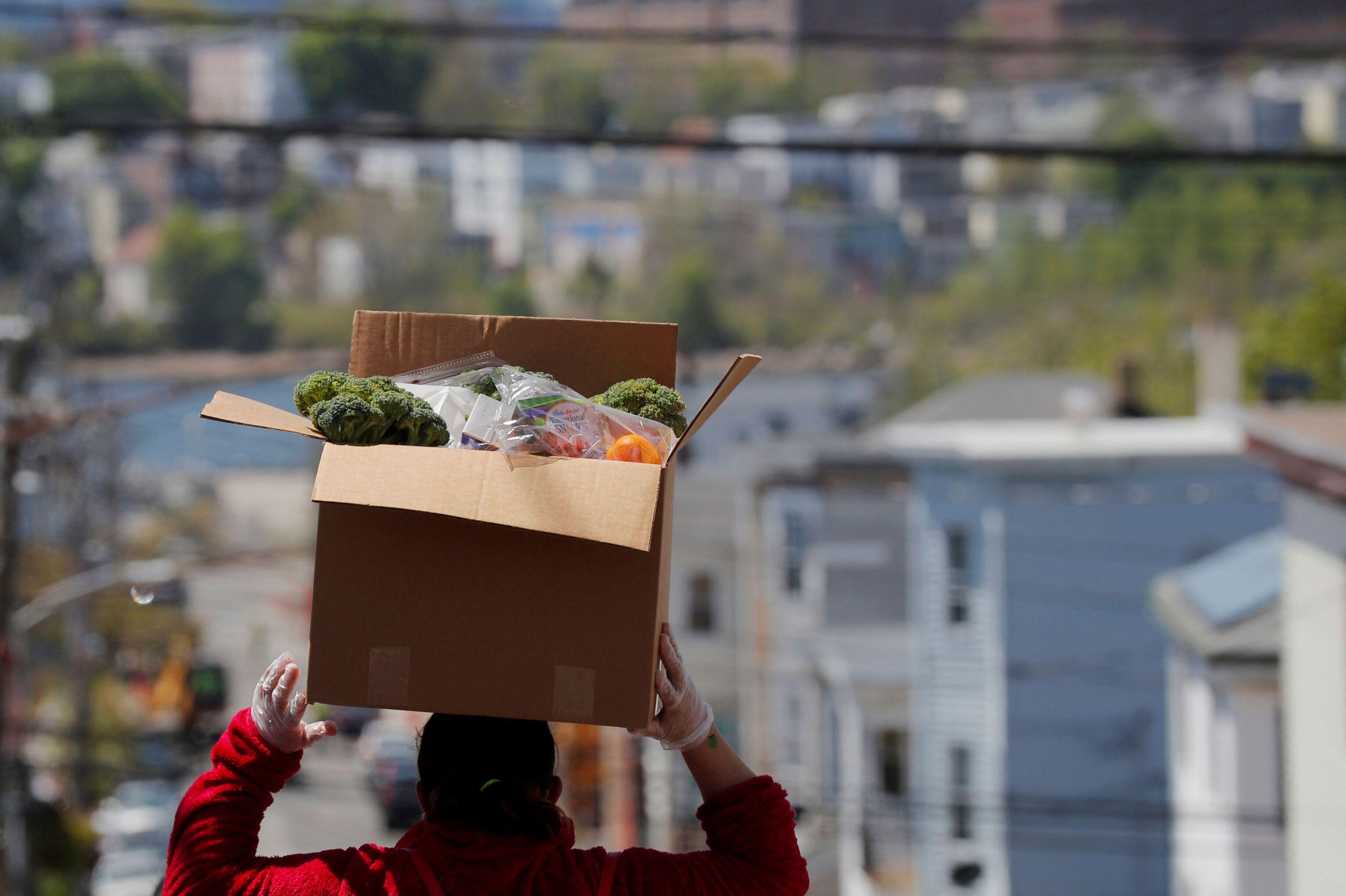 Moradora da cidade de Chelsea leva comida para casa, no estado de Massachusetts, EUA, 19 de maio de 2020