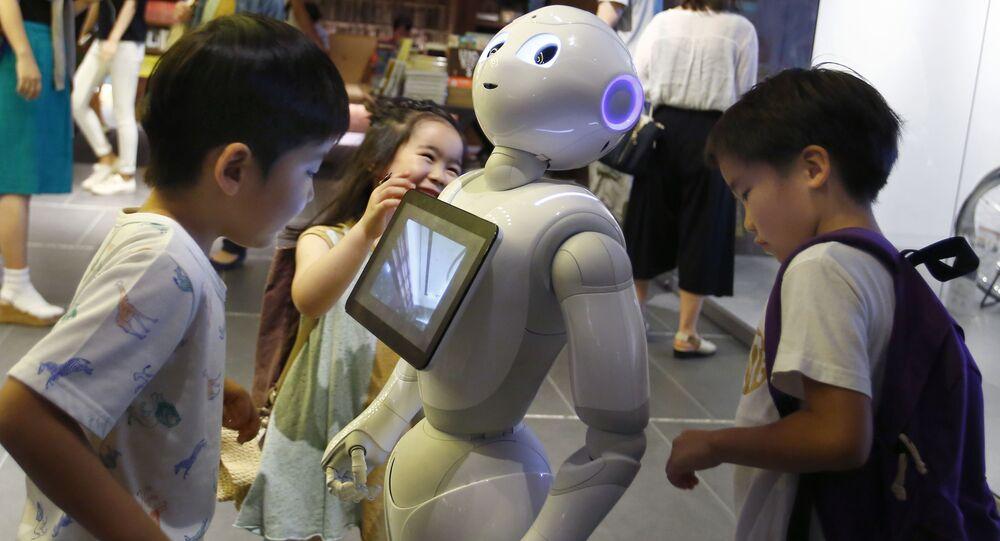 Robô Pepper com crianças no Japão. O robô de altura de 121 cm, maquina equipada com rodas. Pode dançar e falar.