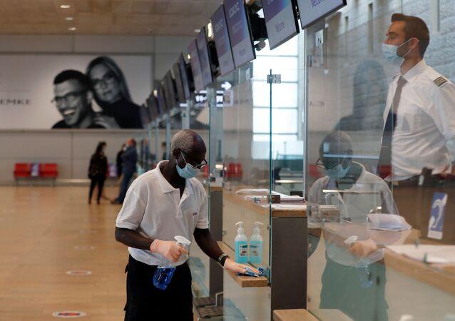 Funcionário desinfecta superfícies em um balcão no terminal de partidas do Aeroporto Internacional Ben Gurion, perto de Tel Aviv, Israel, 14 de maio de 2020.