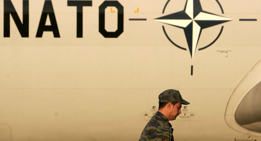 Um membro da Força Aérea da Grécia passa diante de um logo da OTAN em uma aeronave de vigilância AWACS, em 16 de novembro de 2006, na base aérea de Adravida, Grécia.