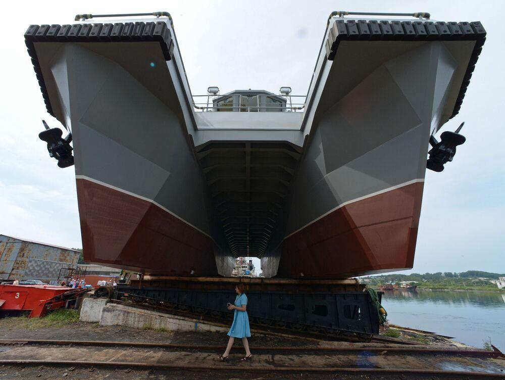 Mulher passa diante de embarcação da Frota do Pacífico