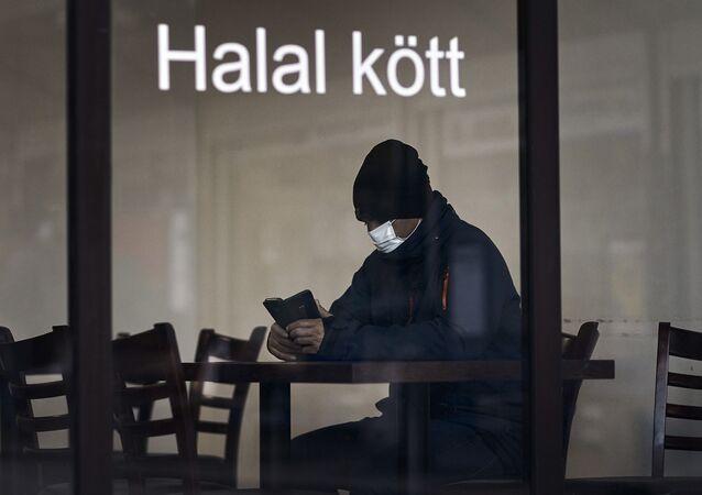 Homem usa máscara para se proteger do coronavírus na Suécia