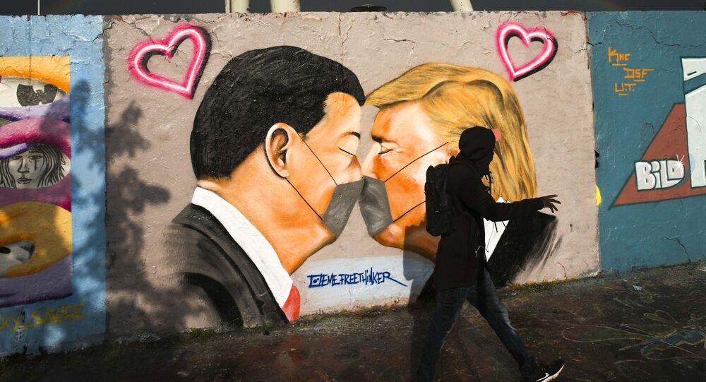 Pedestre passa por muro grafitado com imagem do presidente da China, Xi Jinping, e dos EUA, Donald Trump, em Berlim, Alemanha, 29 de abril de 2020