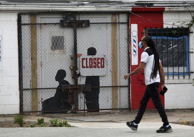 Um pedestre caminha de máscara durante a pandemia da COVID-19 em frente a uma barbearia fechada em Washington, nos EUA, em 8 de maio de 2020.