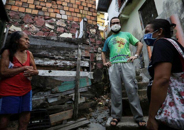 Membros da Igreja Católica conversam sobre a COVID-19 com residente de uma favela em Manaus (AM)