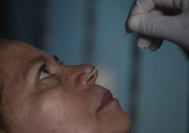 Profissional da saúde faz coleta nasal de mulher na Guatemala