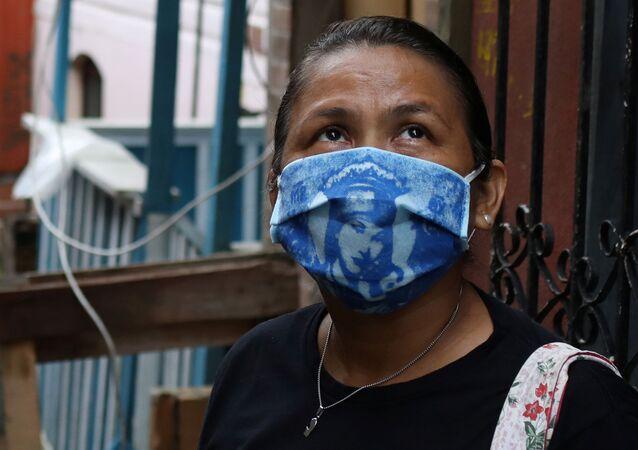 Mulher usa máscara com imagem de santa, na comunidade de Educandos, em Manaus (AM), 19 de maio de 2020